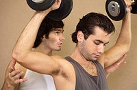 Close-up of a young man exercising with dumbbells and his instructor supporting him from behind