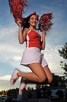 Low angle view of a cheerleader jumping