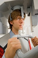 Close-up of a young man going through a medical dental scan by a dental X-Ray equipment