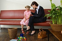 Young woman talking to her daughter in a waiting room (thumbnail)