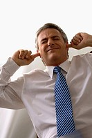 Businessman sitting at a desk and putting his fingers in his ears