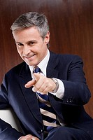 Portrait of a businessman pointing forward and smiling