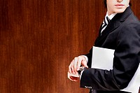 Side profile of a businessman holding an envelope under his arm
