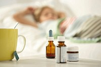 Close-up of a cup with medicine bottles on a table and a girl sleeping on the bed in the background