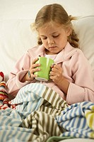 Girl sitting on the bed and holding a cup