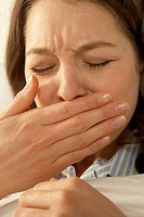 Close-up of a mid adult woman sneezing
