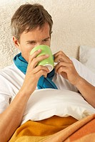 Close-up of a mid adult man reclining on the bed and drinking a cup of tea