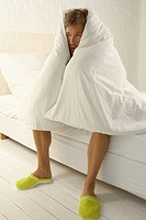 Mid adult man wrapped in a duvet and sitting on the bed