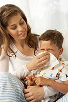 Mid adult woman cleaning her son's nose