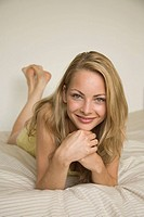 Portrait of a young woman lying on the bed and smiling (thumbnail)