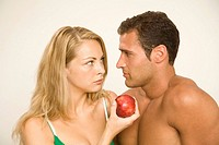 Close-up of a young woman giving an apple to a young man