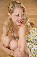 Young woman hugging her knees and smiling