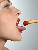 Close-up of a young woman eating a breadstick with sauce
