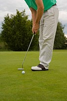 Low section view of a mid adult man playing golf (thumbnail)