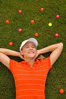High angle view of a mid adult woman lying on grass and smiling (thumbnail)