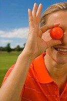 Close-up of a mid adult woman holding a golf ball in front of her eye and smiling