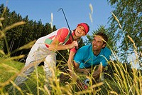 Mid adult couple searching a golf ball in bush (thumbnail)