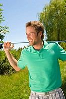 Mid adult man holding a golf club and smiling (thumbnail)