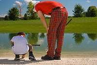 Rear view of a mid adult man playing golf with his son (thumbnail)