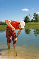 Mid adult man looking at a golf ball trapped in waterhole (thumbnail)