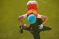 High angle view of a mid adult woman judging a golf ball on a golf course