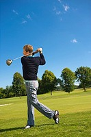 Side profile of a mid adult man swinging a golf club