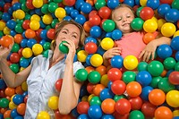 High angle view of a girl with a mid adult woman lying in a ball pool (thumbnail)