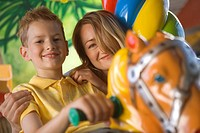 Portrait of a boy sitting on a carousel horse with a mid adult woman behind him