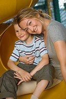 Portrait of a mid adult woman with a boy sitting on a slide and smiling