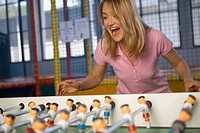 Close-up of a mid adult woman playing foosball