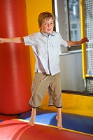 Portrait of a boy jumping on an inflatable bouncy castle