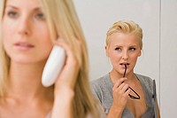 Close-up of a businesswoman talking on a cordless phone with another businesswoman standing behind her