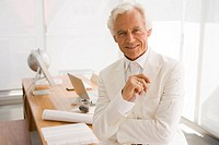 Portrait of a businessman sitting on a desk and smiling in an office (thumbnail)
