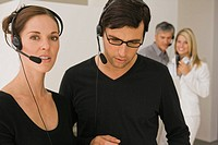 Two customer service representatives wearing headsets in an office