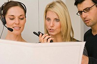 Two businesswomen and a businessman discussing a blueprint in an office