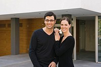 Portrait of a mid adult couple standing in front of a building and smiling