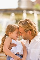 Young man playing with his daughter and smiling (thumbnail)
