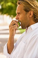 Side profile of a young man eating an apple