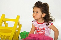 Close-up of a girl sitting on the floor near a chair