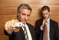 Portrait of a businessman pointing a gun with another businessman smoking a cigar in the background