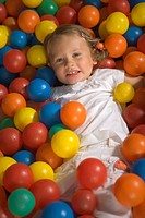 Portrait of a girl lying in a ball pool and smiling