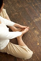 Woman in yoga position, sitting on wooden floor
