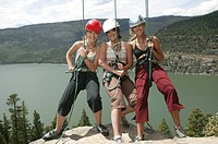 Portrait of three teenage girls 16-17 rock climbing, hanging on ropes, wearing hardhats and harness, smiling , river in background
