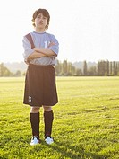 Boy 10-11 in football uniform standing with arms crossed in field