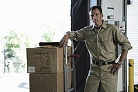 Delivery man standing with boxes in loading bay, portrait