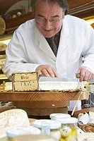Mature man cutting brie cheese in shop