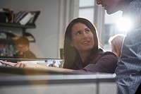 Woman sitting at desk talking to man at office lens flare