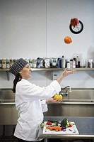 Female chef juggling vegetables in kitchen, profile