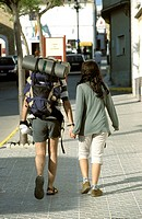 backpackers walking hand-in-hand in conil de la frontera