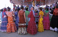 Sanlucar de Barrameda, a group of women in flamenco dress watching a merry go round